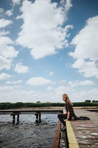 Kaboompics - Beautiful blonde woman on a wooden pier by the lake