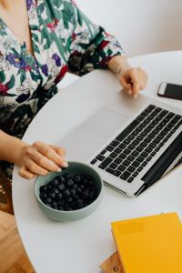 Kaboompics - A woman eats blueberries and works on a laptop