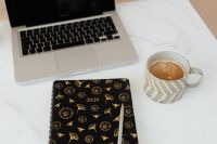 Laptop - organizer - pen & cup of coffee on marble table