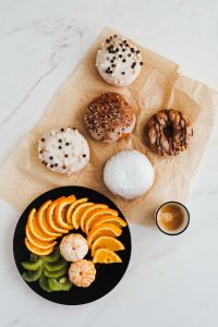 Kaboompics - Donuts, coffee & plate with fruits: orange, madarine, kiwi