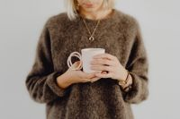 Kaboompics - A woman in a brown sweater holds a pink, minimalist mug