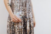 Kaboompics - Woman in a Sequin Dress is Holding a Glass of Champagne, White Background