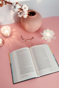 Kaboompics - An open book, candles, cotton branch and glasses on a pink background
