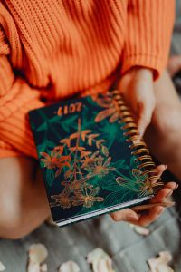 Kaboompics - A woman in an orange sweater holds the 2019 calendar in her hands