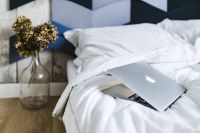 An ornamental golden plant in a jar by the bed with white sheets and a laptop