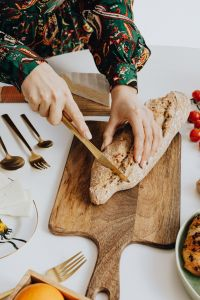 Kaboompics - Woman is cutting bread on cutting board