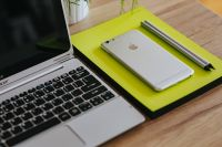Kaboompics - Silver Acer laptop, a white Apple iPhone and a yellow notebook on a wooden desk