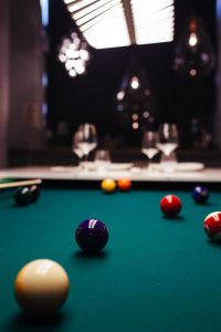Billiard balls on green table with billiard cue