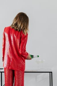Kaboompics - Woman in a red jacket holds a bottle of champagne