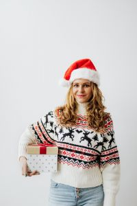 Kaboompics - Woman with Gift Wearing Christmas Sweater and Santa Hat