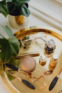Kaboompics - Makeup essentials on a golden tray