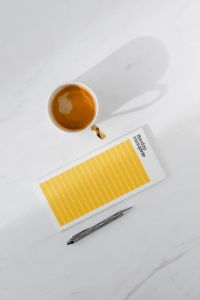 Kaboompics - Top view of a marble desk with coffee, notebooks and pen