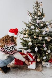 Kaboompics - Woman with Gift Wearing Christmas Sweater and Santa Hat, Christmas Tree Background
