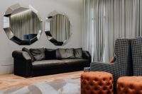 Black leather sofa and big mirrors in living room.