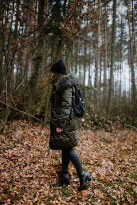 Kaboompics - A woman dressed in a green jacket, a black hat and black trousers with a black backpack in the forest