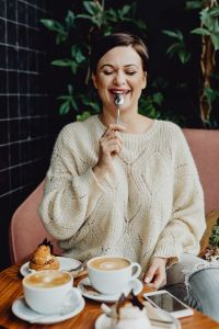 Kaboompics - A woman drinks coffee and eats a dessert in a café