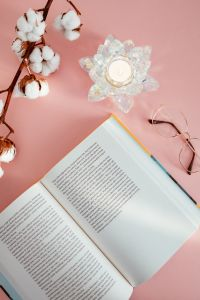 Kaboompics - An open book, candle, glasses and a cotton branch on a pink background