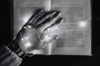 Kaboompics - Female hand, fairy lights, book