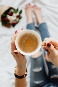 Kaboompics - Woman with coffee and flowers in bed