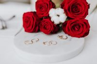 Red roses and gold rings on white marble