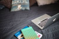 Kaboompics - Laptop with books on a bed