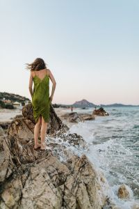 Kaboompics - A woman in a green dress on a rock by the sea