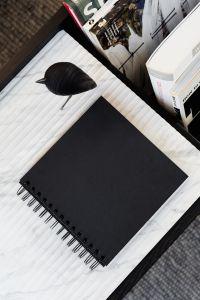 Kaboompics - blackbook & wooden bird on marble