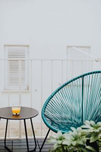 A stylish garden chair and a small table on the balcony