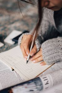 Kaboompics - Woman in a grey sweater taking notes in an organizer