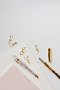 Fountain pens, clips and notebooks on a white desk