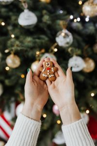Kaboompics - Woman holds a gingerbread cookie, Christmas tree background