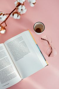 Kaboompics - An open book, coffee, glasses and a cotton branch on a pink background