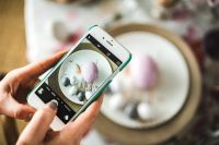 Woman taking photo of easter eggs on a plate