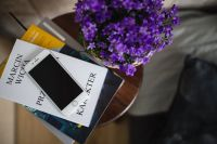 Kaboompics - Books, purple flowers and a white smarphone on a wooden stool by the bed