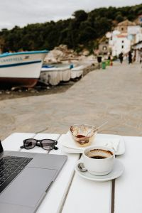 Kaboompics - Working with a laptop by the sea. Cup of coffee and delicious tiramisu, Marina di Puolo, Italy