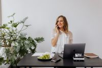 A businesswoman speaks on the phone at her desk