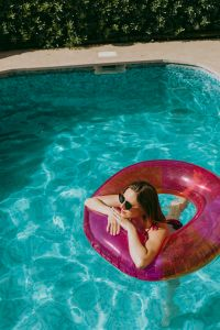 Kaboompics - A beautiful woman in a pool with an inflatable ring