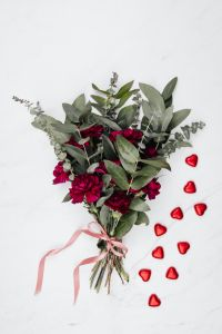 Kaboompics - A bouquet of flowers and a red heart-shaped pralines on white marble