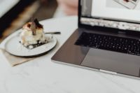 Kaboompics - Working with a laptop, meringue with whipped cream on white marble