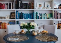 Kaboompics - Round breakfast table with white flowers by the bookcase