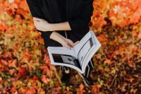 Kaboompics - Girl with the Grafconf book on the background of coloured leaves