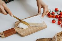 Woman is cutting cheese on cutting board