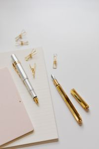 Kaboompics - Fountain pens, clips and notebooks on a white desk