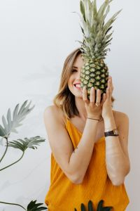 Kaboompics - A beautiful smiling young woman is holding a pineapple