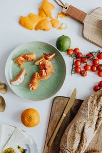 Kaboompics - Orange - tomatos - bread -  cutting board ona table