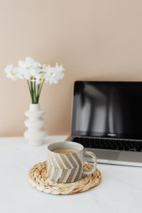 Laptop - white flowers & cup of coffee on marble table