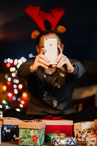 A handsome man with Christmas presents takes pictures with his phone