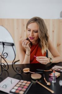 Kaboompics - Young woman sitting and doing makeup in front of mirror