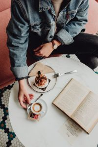 Kaboompics - A woman eats meringue, drinks coffee and reads a book in a patisserie