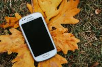 Kaboompics - White smartphone on a yellow leaf